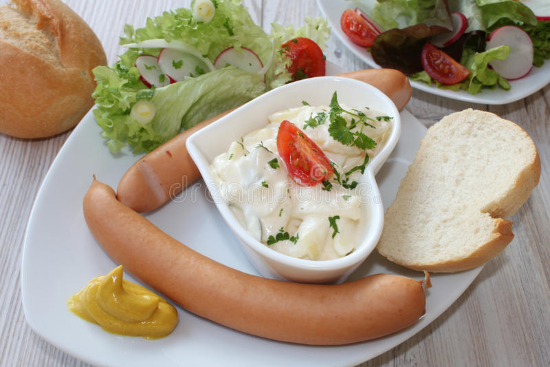 Kleine worst met salade en brood stock afbeelding