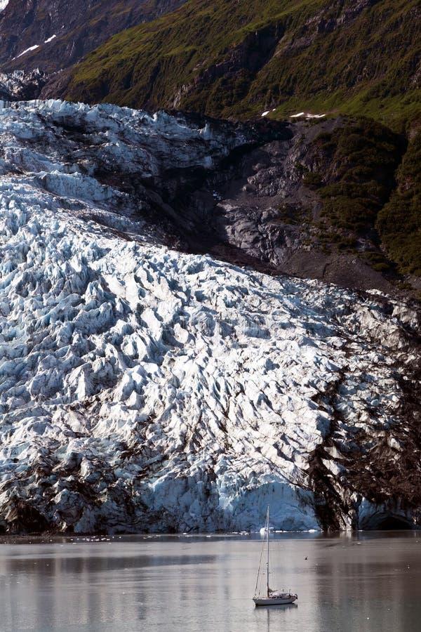 Kleine Yacht in den Schatten gestellt durch enormen Gletscher stockbild