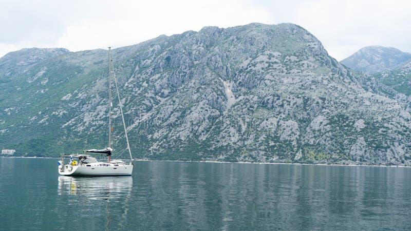 Kleine Yacht in der Bucht von Kotor in Montenegro Marine Boats Entspannungslandschaft, Boot in einem ruhigen See Grauer Berg mit  lizenzfreie stockfotos