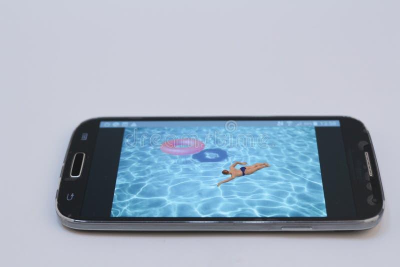 kleine Zahl Ralaxing im Pool Ansicht über Tastatur und Schirm lizenzfreie stockfotografie