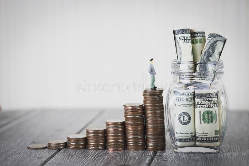 Kleine Zahl Stand der Miniaturleute auf Münzgeldstapel steigern wachsendes Wachstumseinsparungsgeld mit hundert Dollar lizenzfreie stockbilder