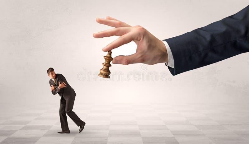 Kleine zakenman die vanaf grote hand met schaakstukconcept lopen stock afbeeldingen