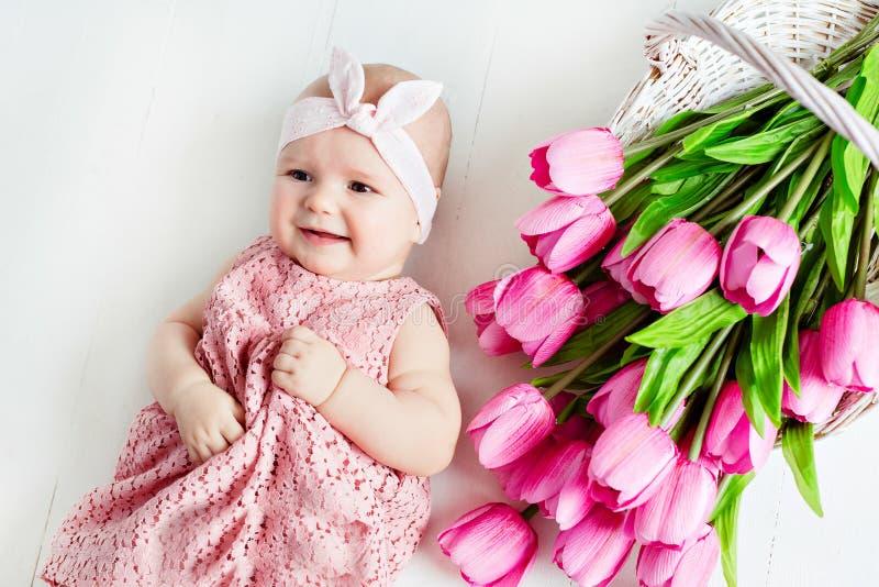 Kleine zeer leuk, groot-eyed weinig babymeisje in het roze kleding liggen stock fotografie