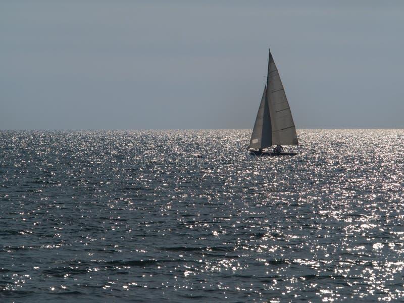 Kleine zeilboot die in een fonkelende overzees varen stock fotografie