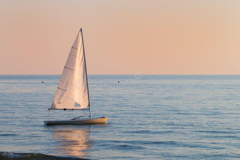 Kleine zeilboot in het water naast het strand royalty-vrije stock afbeelding