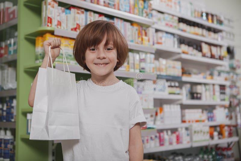 Kleine zieke jongen bij de apotheek stock afbeelding