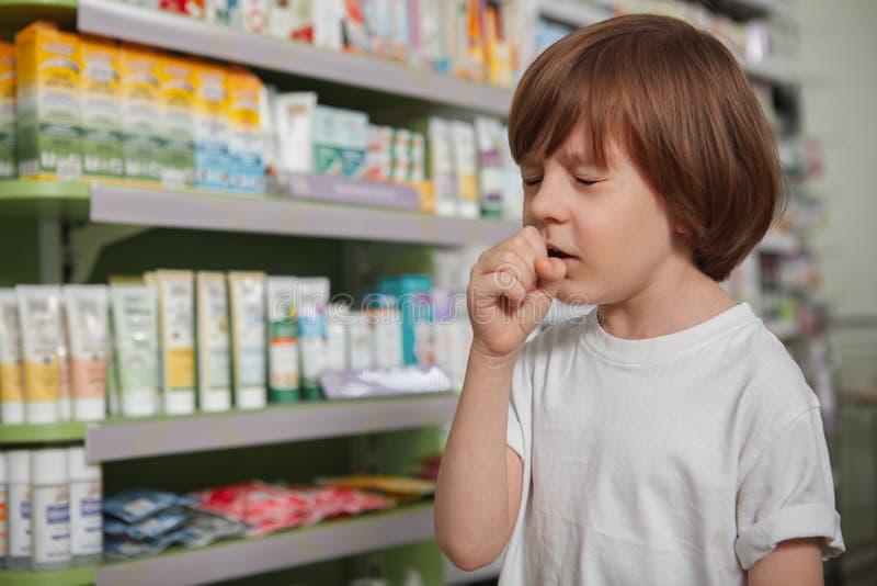 Kleine zieke jongen bij de apotheek stock fotografie