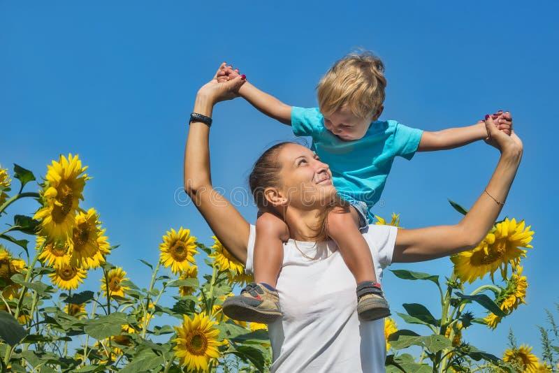 Kleine zoon met mum onder zonnebloemen royalty-vrije stock foto's