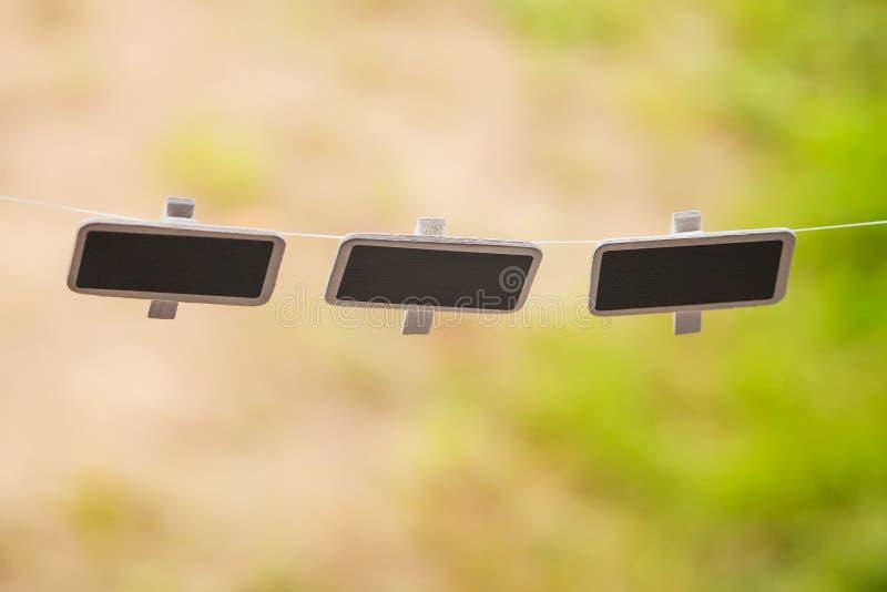Kleine zwarte borden die in openlucht hangen stock foto's