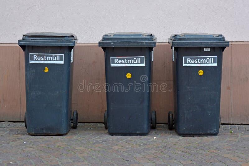 3 kleine zwarte overblijvende afvalbakken op wielen die zich op een rij op huismuur bevinden in stad royalty-vrije stock afbeeldingen