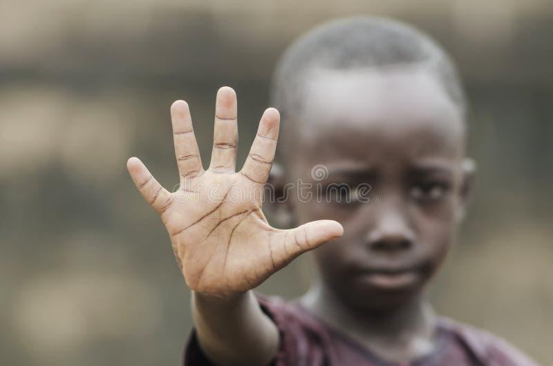 Kleiner afrikanischer Junge, der Palme als Stoppschild zum Rassismus, zum Krieg und zum Kampf zeigt lizenzfreie stockbilder