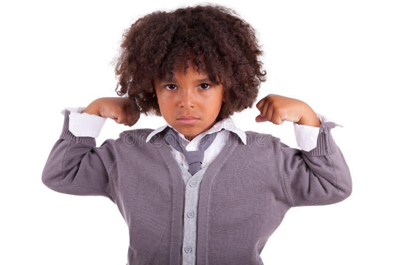 Kleiner afrikanischer Junge, der seine Muskeln zeigt stockfoto