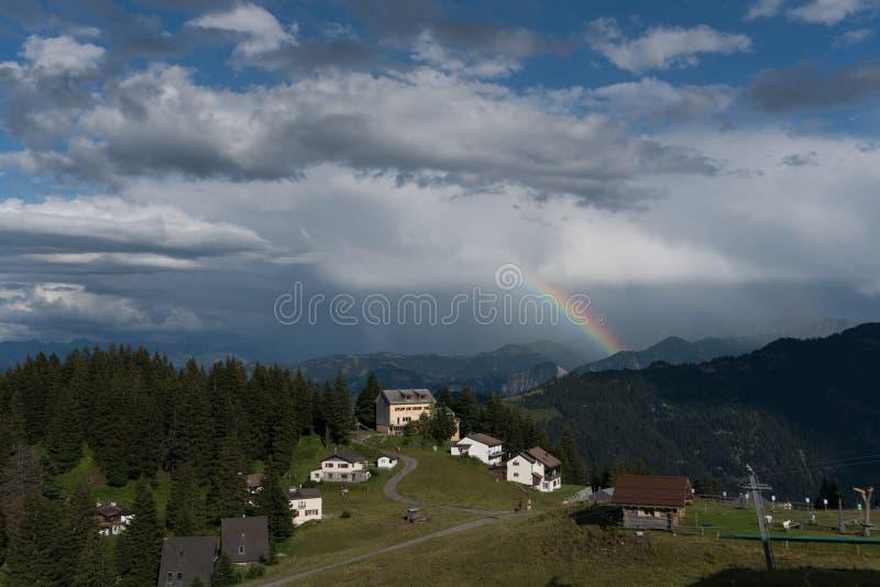Kleiner alpiner Dorf- und Skiaufzug in den Schweizer Alpen mit einer großen Ansicht eines Regenbogens und der Berglandschaft stockfotos