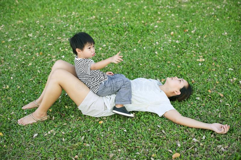 Kleiner asiatischer Junge, der auf seiner Mutter im Garten zeigt und sitzt stockfotos