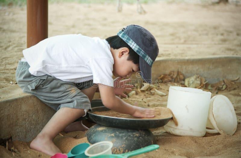 Kleiner asiatischer Junge, der im Sandkasten spielt: Nahaufnahme lizenzfreie stockfotografie