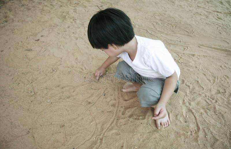 Kleiner asiatischer Junge, der Sand spielt lizenzfreie stockfotografie