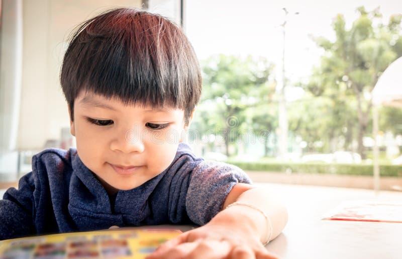 Kleiner asiatischer Junge liest ein Buch lizenzfreie stockbilder