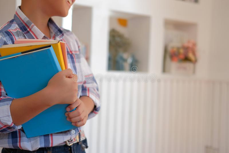 kleiner asiatischer Kinderjungenkinderkinderschüler, der Bücher hält chi lizenzfreies stockfoto