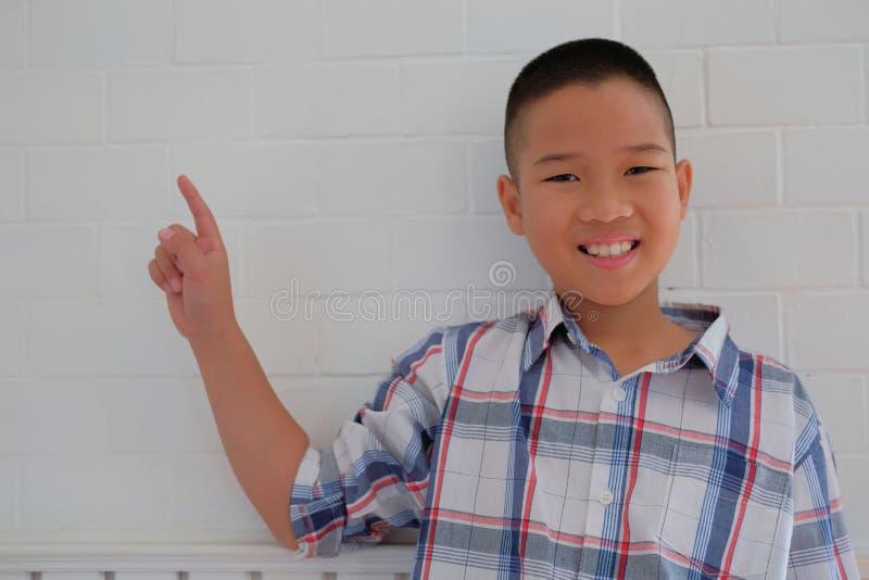 kleiner asiatischer lächelnder u. zeigender Kinderjungenkinderkinderschüler lizenzfreie stockfotografie