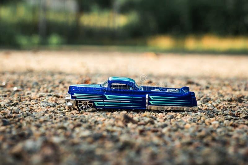 Kleiner blauer Spielzeugkleintransporter auf kleinen Marmorfelsen stockfotos