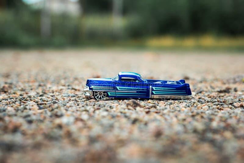 Kleiner blauer Spielzeugkleintransporter auf kleinen Marmorfelsen lizenzfreies stockbild