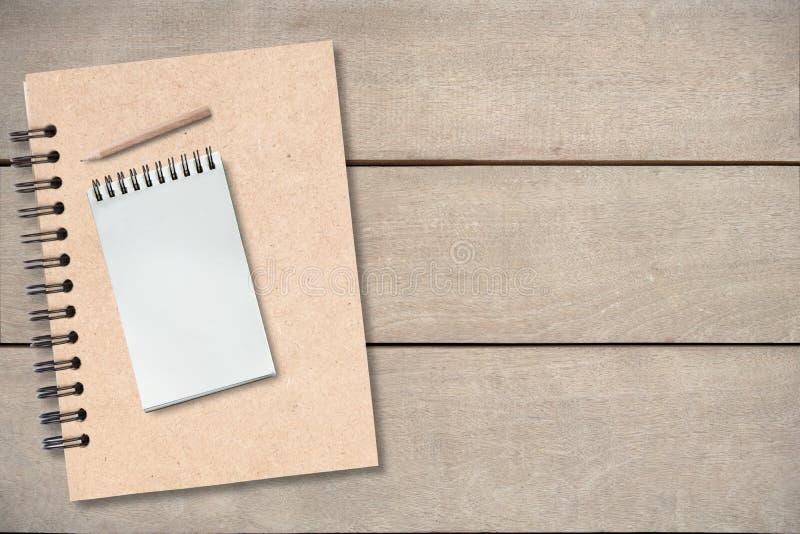 Kleiner Bleistift auf leerem Buch auf Holztisch, Draufsichthintergrund, Kopienraum, Schein oben lizenzfreie stockfotografie