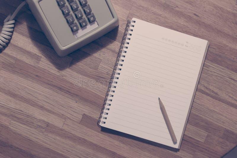 Kleiner Bleistift auf leerem Notizbuch mit Weinleseskalatelefon lizenzfreies stockfoto