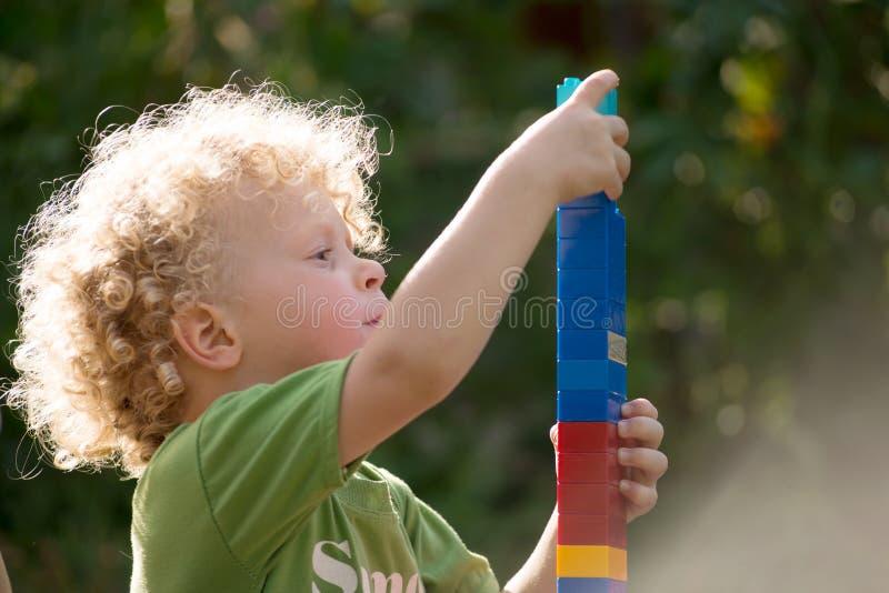 Kleiner blonder Junge, der mit Blöcken spielt stockbilder