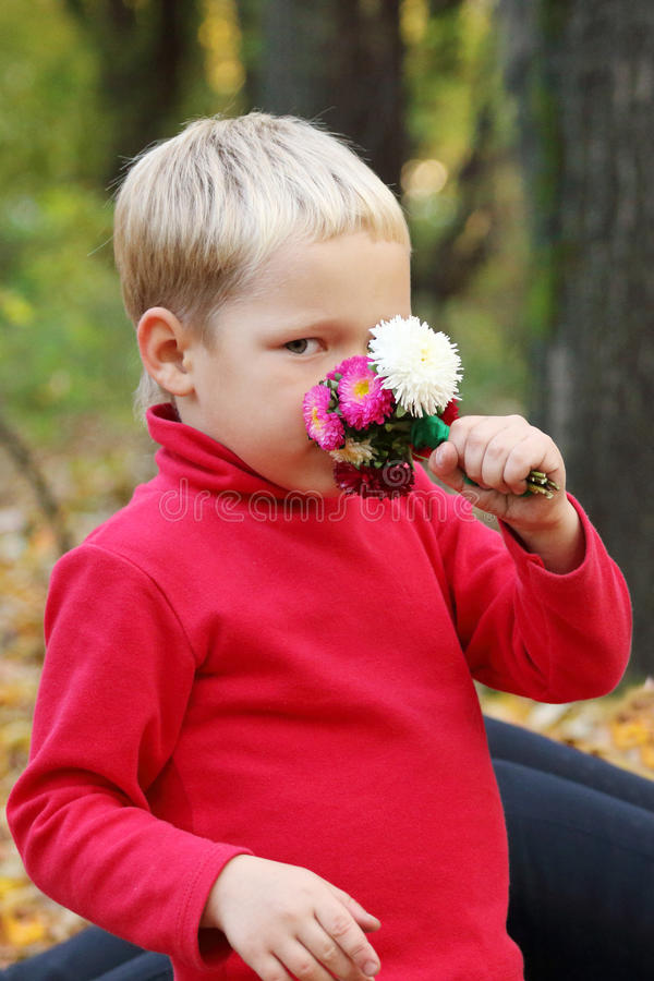 Kleiner blonder Junge im Rot schnüffelt Blumen stockfotografie
