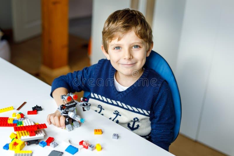 Kleiner blonder Kinderjunge, der mit vielen bunten Plastikblöcken spielt lizenzfreies stockfoto
