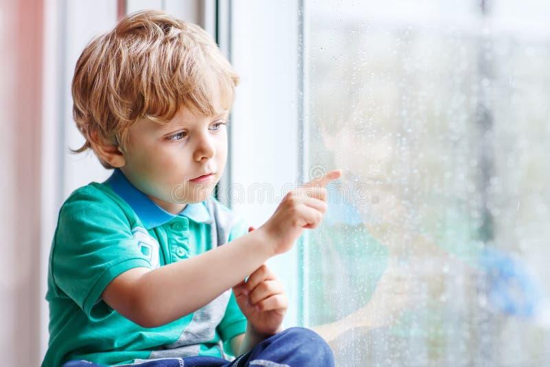 Kleiner blonder Kinderjunge, der nahe Fenster sitzt und auf Regentropfen schaut stockfotografie
