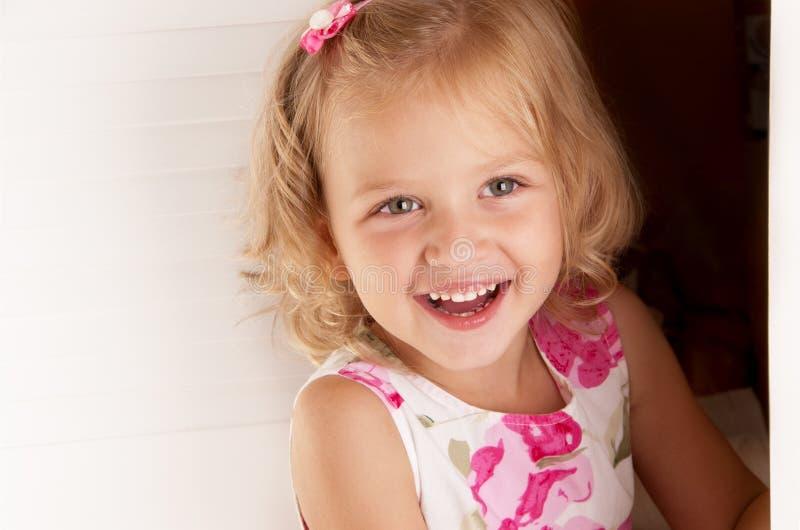 Kleiner blonder Mädchenblick aus der Tür heraus lizenzfreies stockfoto