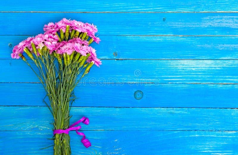 Kleiner Blumenstrauß von roten Gartennelken auf den blauen schäbigen Brettern stockbild