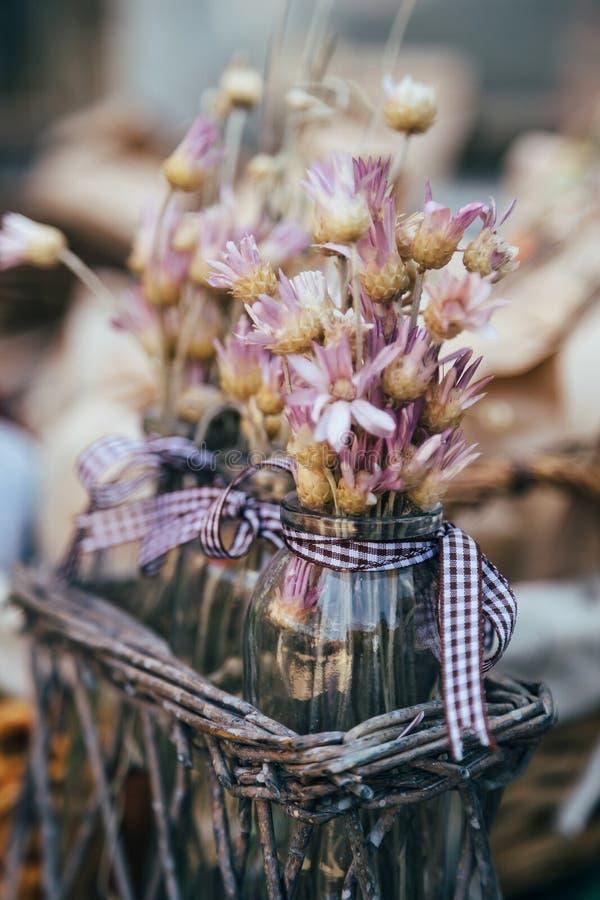 Kleiner Blumenstrauß von trockenes immortelle wilden Blumen in den violetten, rosa Farben in den kleinen Glasvasen draußen Beschn stockbild