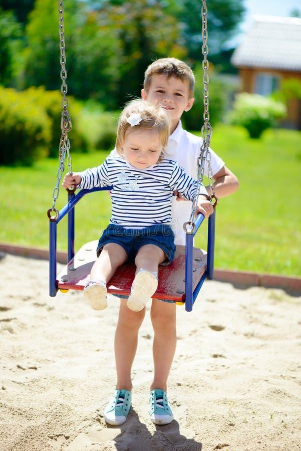 Kleiner Bruder und die Schwester, die im Sommer schwingt, parken lizenzfreies stockfoto