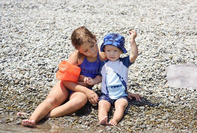 Kleiner Bruder und Schwester auf dem Strand lizenzfreie stockbilder