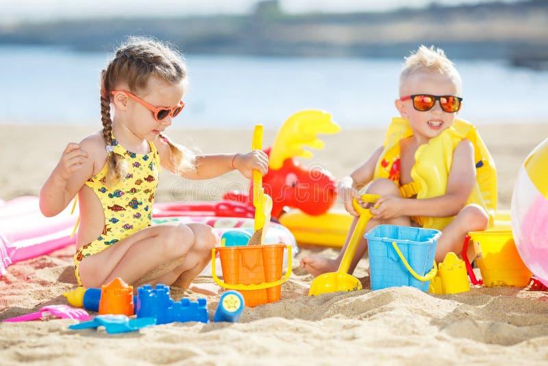 Kleiner Bruder und Schwester, die auf dem Strand im Sand spielt stockbild
