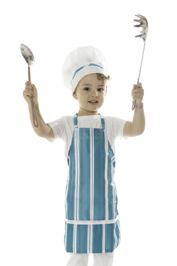 Kleiner Chef mit Küchenwerkzeugen stockfotos