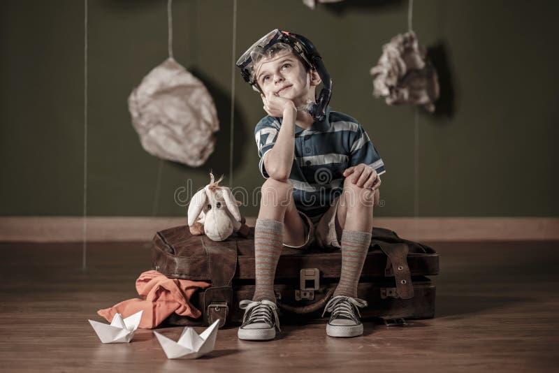 Kleiner Daydreamer, der auf Koffer sitzt lizenzfreie stockfotos