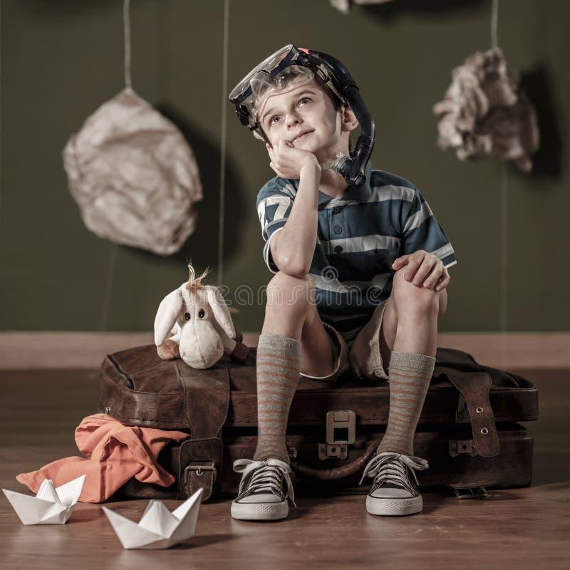 Kleiner Daydreamer, der auf Koffer sitzt stockbilder