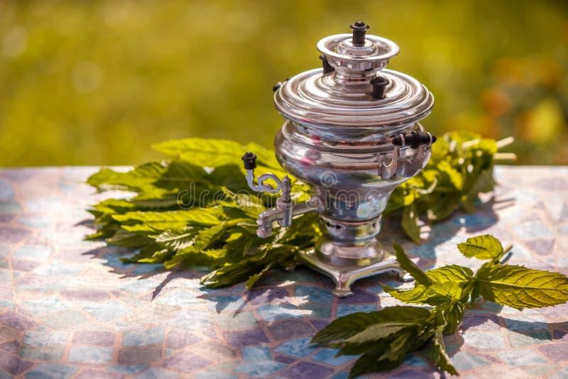 Kleiner dekorativer Samowar und tadellose Blätter zu einer Tasse Tee auf blauen Tischdecken lizenzfreies stockbild