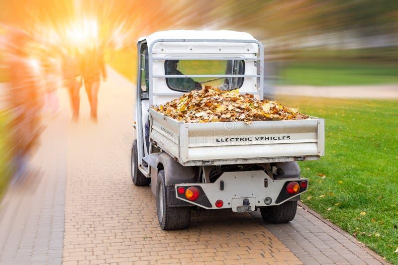 Kleiner elektrischer LKW, der gefallene Blätter im Körper am Herbststadtpark entfernt Städtischer Stadtverkehr mit grünem Fahrzeu lizenzfreie stockfotos