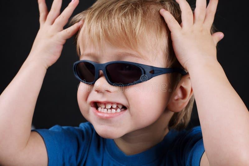 Kleiner emotionaler Junge mit Sonnenbrille lizenzfreie stockfotografie