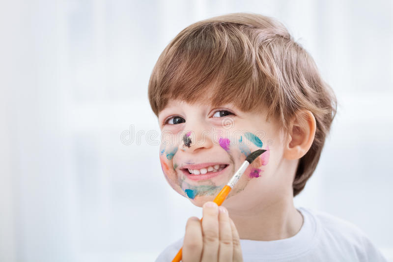 Kleiner entzückender Kinderjunge, der eine Verwirrung mit Farben auf seinem Gesicht macht stockfoto