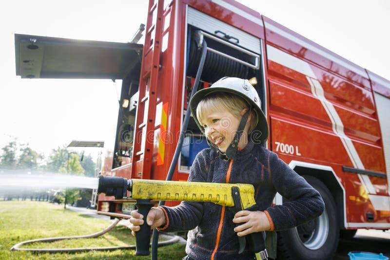 Kleiner Feuerwehrmann, der firehose D?se und Spritzwasser h?lt stockbild