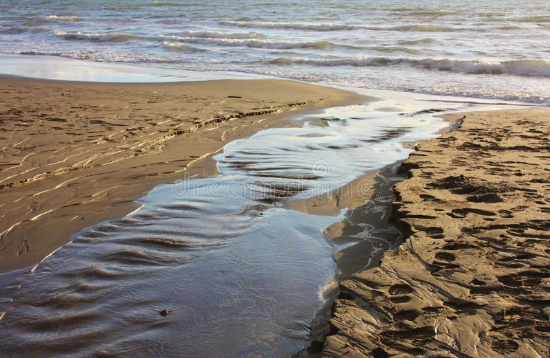 Kleiner Fluss gosse Verlust des Wassers Unterbrochenes Rohr strömendes Wasser auf dem Ufer des Strandes, das Meer, auf dem Sand lizenzfreie stockfotografie