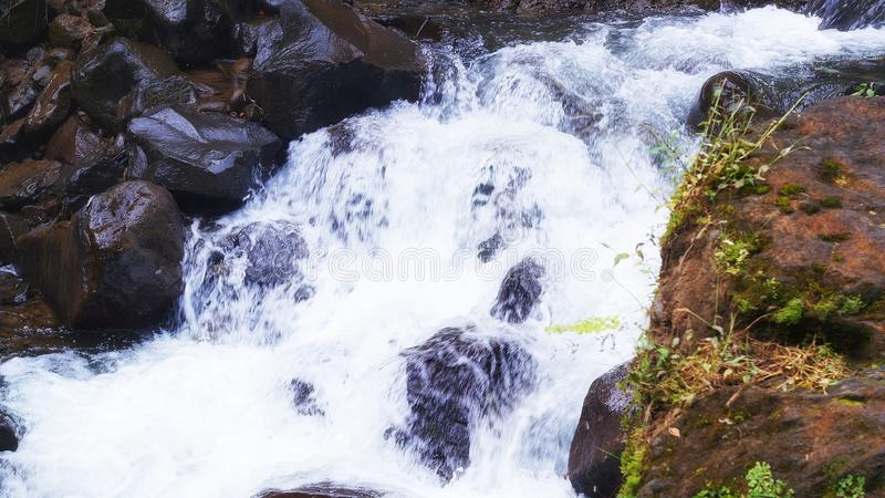 Kleiner Fluss unter einem Wasserfall lizenzfreie stockbilder