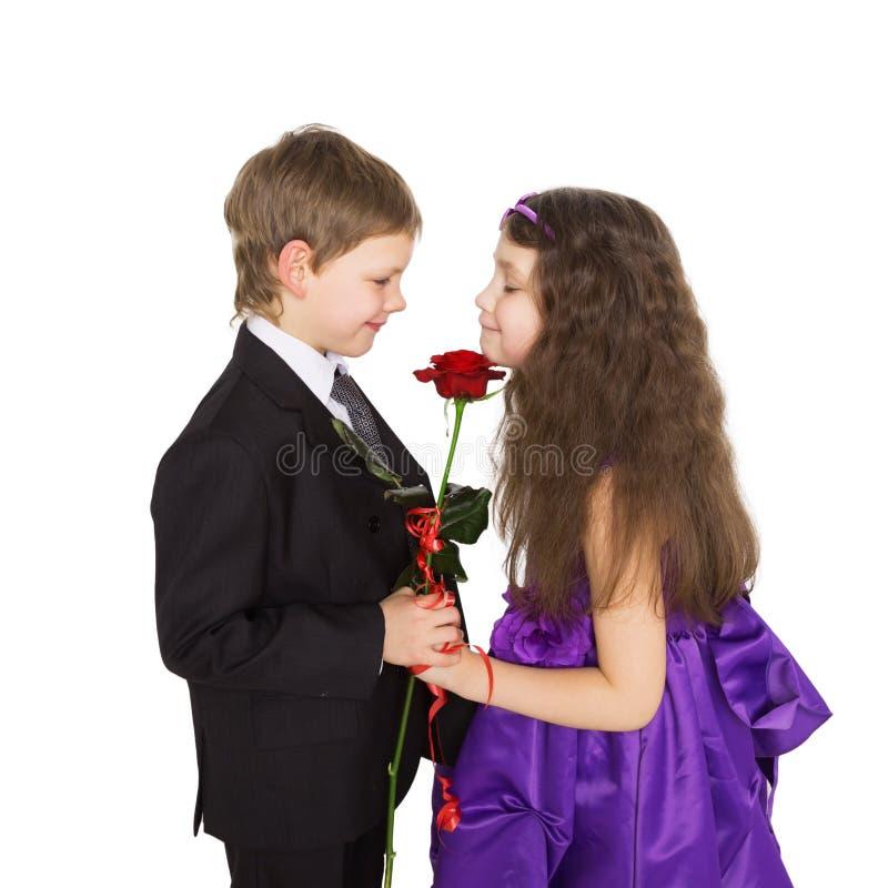 Kleiner Freund gibt der Freundin eine Blume lizenzfreies stockbild