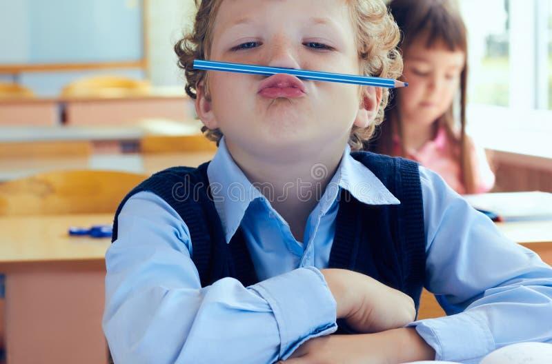 Kleiner gelockter Schüler hat Spaß zwischen Lektionen in der Grundschule stockfotos