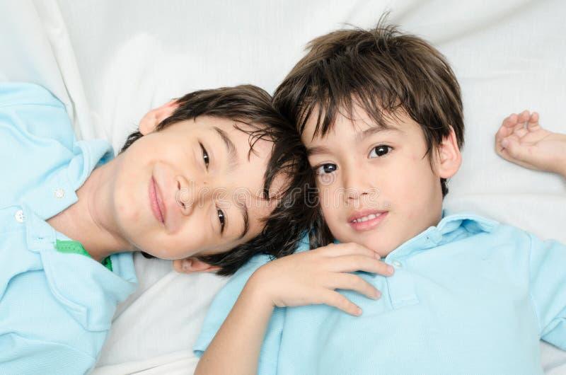 Kleiner Geschwisterjunge, der auf dem Bett niederlegt lizenzfreies stockbild